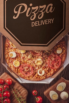 Pizza brésilienne avec mozzarella, maïs, bacon, œufs, tomate et origan dans une boîte de livraison (pizza especial) - vue de dessus.