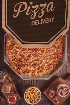 Pizza brésilienne avec mozzarella, maïs, bacon et origan dans une boîte de livraison (pizza de milho com bacon) - vue de dessus.