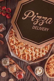 Pizza brésilienne avec mozzarella, poulet, catupiry et origan dans une boîte de livraison (pizza de frango com catupiry) - vue de dessus.