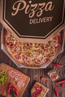Pizza brésilienne à la mozzarella, saucisse calabrais, poivron vert, oignon et piment calabrais dans une boîte de livraison (pizza de calabresa picante) - vue de dessus.