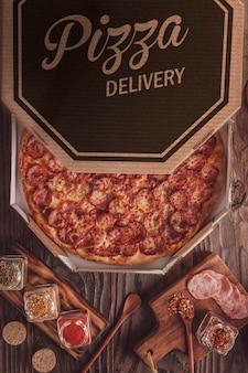 Pizza brésilienne avec mozzarella, saucisse calabrese et origan dans une boîte de livraison (pizza de calabresa) - vue de dessus.