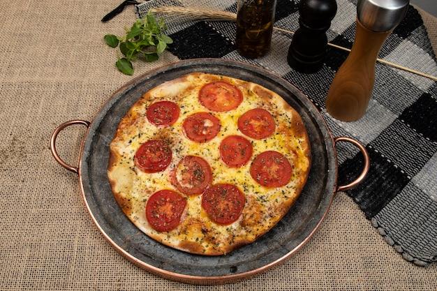 Pizza brésilienne napolitaine avec fromage mozzarella et tranches de tomates à l'origan, vue de dessus