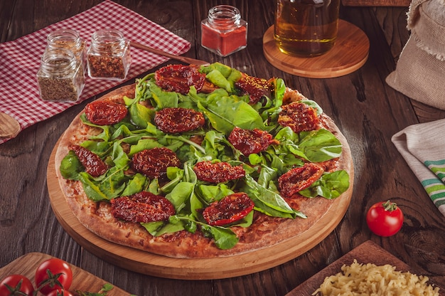 Pizza brésilienne avec sauce tomate, mozzarella, roquette, tomates séchées et origan (pizza de rucula com tomate seco)