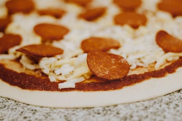 Pizza con queso parmesano, peperoni y tomate sin cocinar