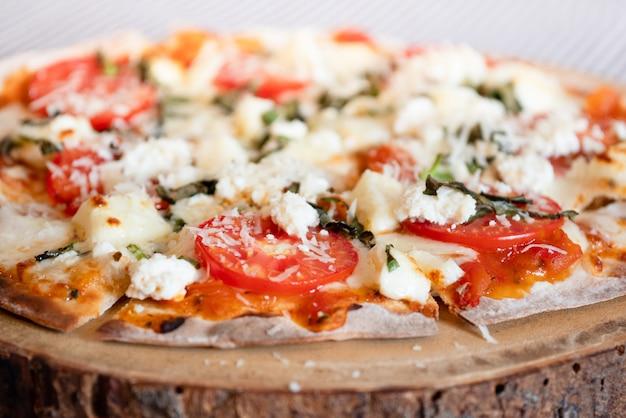 Pizza croustillante faite maison sur un morceau de bois, style de cuisine confortable