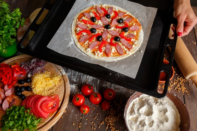 Pizza crue avec des ingrédients sur une plaque à pâtisserie