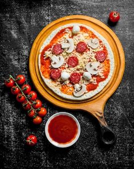 Pizza crue avec saucisses, fromage et champignons sur table rustique