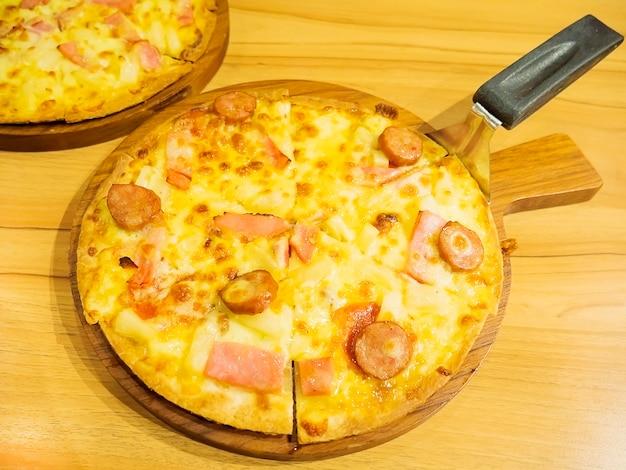 Pizza et cuillère sur plateau en bois