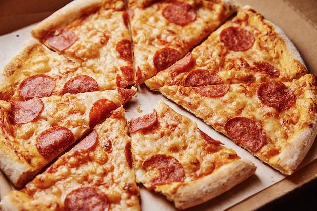 Pizza dans une boîte en carton avec une tranche mordue, gros plan