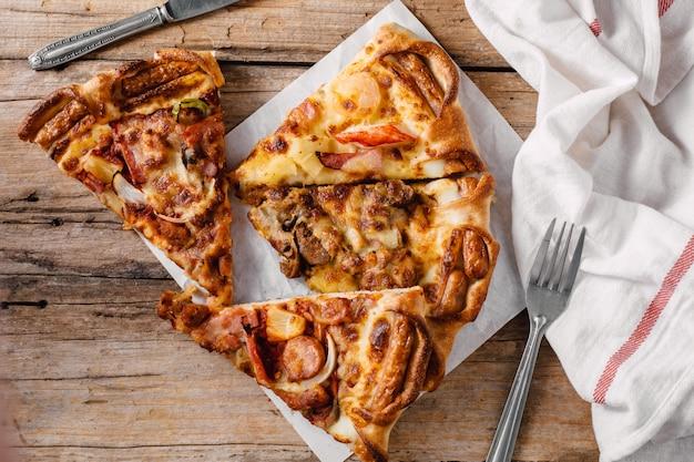 Pizza dans la boîte de papier sur la table en bois