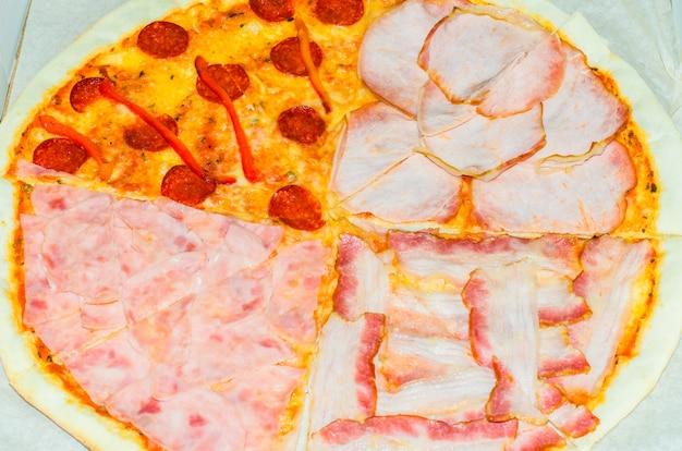 Une pizza entière avec quatre garnitures différentes