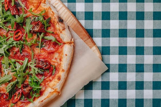 Pizza épicée napolitaine avec jambon, fromage, roquette, basilic, tomates, poivrons pepperoni au fromage
