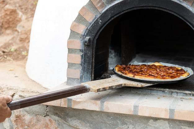 Pizza faite dans un four à bois artisanal peint en blanc construit à l'extérieur, arrière-plan