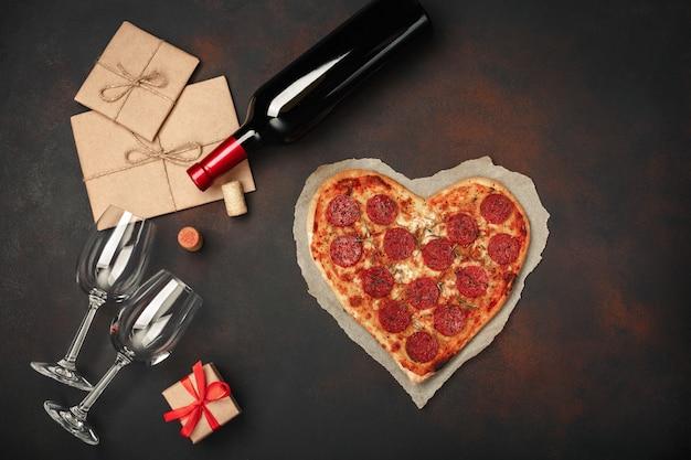 Pizza en forme de coeur avec mozzarella, saucisse, bouteille de vin, deux verres à vin, coffret cadeau sur fond rouillé