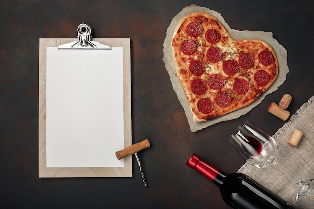 Pizza en forme de coeur avec mozzarella, saucisse, bouteille de vin et tablette