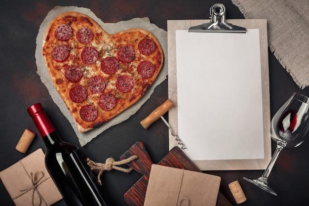 Pizza en forme de coeur avec mozzarella, saucisse, bouteille de vin, tire-bouchon et tablette sur fond rouillé