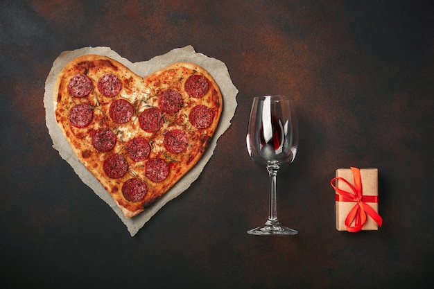 Pizza en forme de coeur avec mozzarella, saucisse, verre à vin, coffret cadeau sur fond rouillé