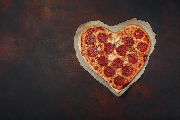 Pizza en forme de coeur avec mozzarella et saucisse.
