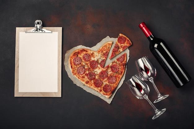 Pizza en forme de coeur avec mozzarella, saucisson, bouteille de vin, deux verres à vin et tablette sur fond rouillé