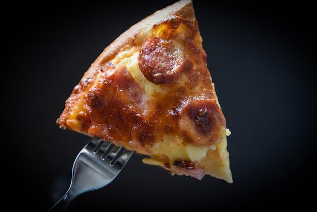 Pizza sur fourchette / tranche de pizza sur le noir foncé