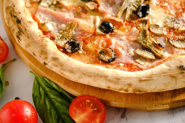 Une pizza fraîche et appétissante est sur la table. nourriture d'un restaurant italien. cuisson des pizzas. ingrédients des pizzas. dîner entre amis.