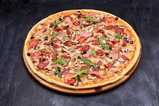 Pizza fraîche campania sur une planche à découper en bois. isolé sur fond sombre.