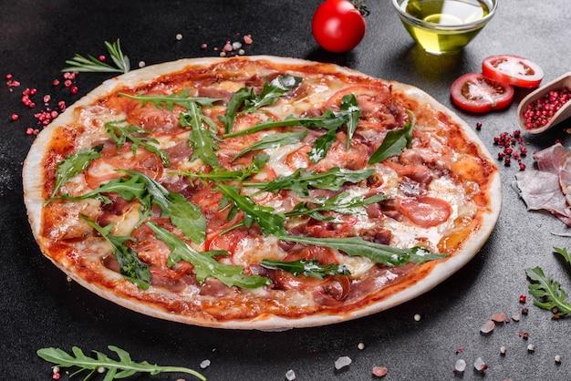 Pizza fraîche cuite au four avec roquette, salami, tomates cerises et mozzarella. cuisine italienne