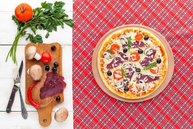 Pizza Fraîche Dans Un Style Italien Rustique Avec Des Champignons D'olives Séchées Et Trois Sortes De Fromage Sur Un Fond En Bois Clair Photo Premium
