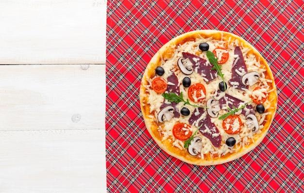 Pizza fraîche dans un style italien rustique avec des champignons d'olives séchées et trois sortes de fromage sur un fond en bois clair