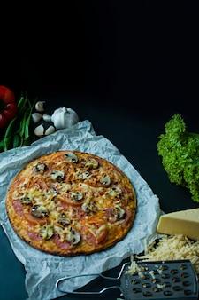 Pizza fraîche avec des saucisses, des tomates, des champignons et du fromage sur une surface sombre