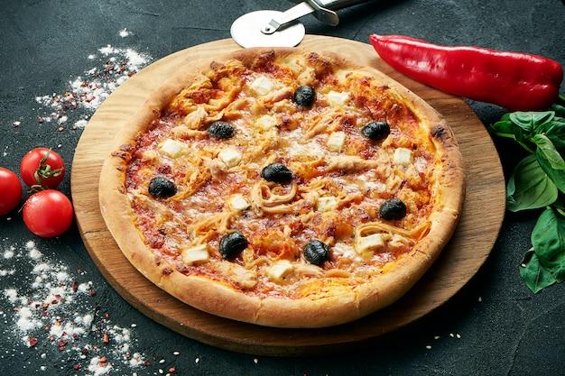 Pizza avec un grand nombre de garnitures: poulet, oignons, champignons, olive. pizza en composition avec des ingrédients sur un tableau noir