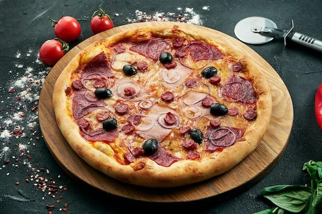 Pizza avec un grand nombre de garnitures: saucisses de chasse, oignons, champignons, salami, fromage et poivron. pizza en composition avec des ingrédients sur un tableau noir