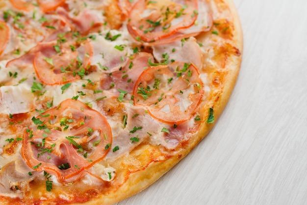 Pizza gros plan sur une surface en bois blanche