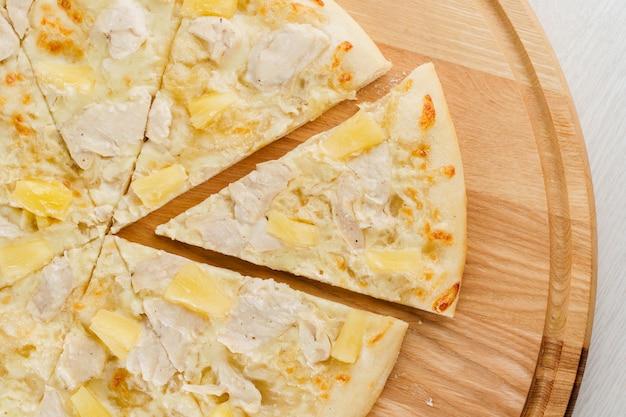 Pizza hawaïenne à l'ananas, poulet, fromage et sauce isolé sur une surface en bois blanc