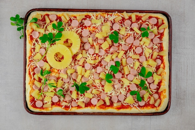 Pizza hawaïenne avec saucisses et tranches d'ananas sur le plateau.