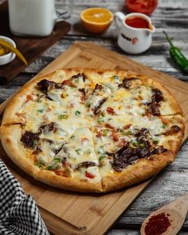 Pizza avec des ingrédients mélangés sur une planche de bois.