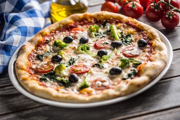 Pizza irlandaise avec brocoli épinards tomates olives et mozzarela ou parmesan. repas végétarien méditerranéen.