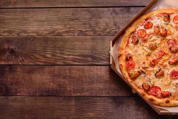 Pizza italienne aux fruits de mer avec crevettes, calamars, moules, herbes fraîches et mozzarella