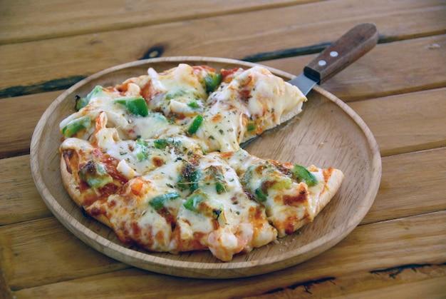 Pizza italienne aux fruits de mer et fromage mozzarella sur une planche à découper en bois avec une table en bois