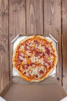 Pizza italienne dans une boîte en carton sur table en bois. vue de dessus.