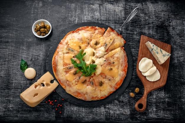 Pizza italienne avec différentes sortes de fromage sur une pierre et un tableau noir rayé.