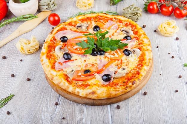 Pizza italienne sur un fond en bois avec décoration autour