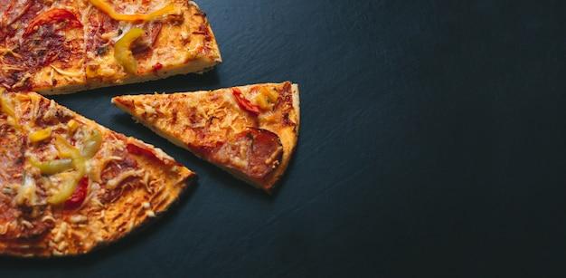 Pizza italienne sur fond noir avec vue de dessus. espace pour le texte