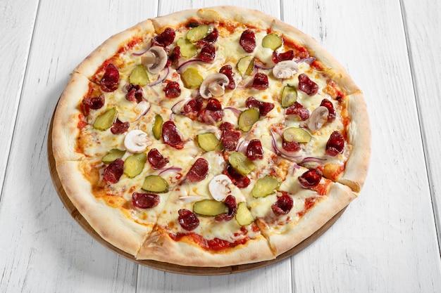 Pizza italienne fraîche aux champignons et saucisses sur table en bois