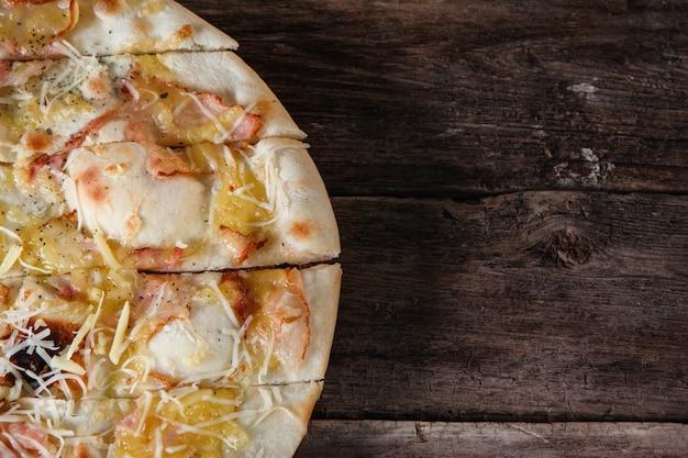 Pizza italienne fraîche avec bacon, jambon et fromage servie sur une table en bois rustique, mise à plat. malbouffe, mauvaises habitudes, calories. fond sombre avec espace libre pour le texte.