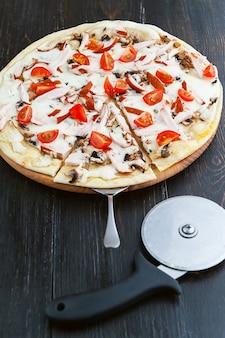 Pizza italienne fraîche et délicieuse sur une table en bois et un couteau à pizza