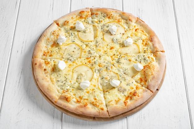 Pizza italienne fraîche avec différents types de fromage et tranches de poire sur table en bois