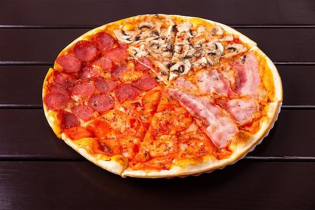 Pizza italienne fraîche des quatre saisons ou pizza quattro stagioni sur la table de cuisine en bois