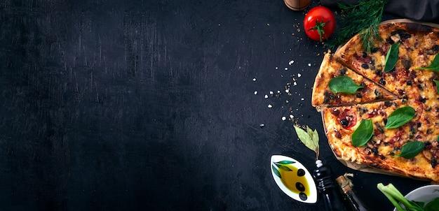 Pizza italienne et ingrédients de cuisson de pizza sur fond sombre