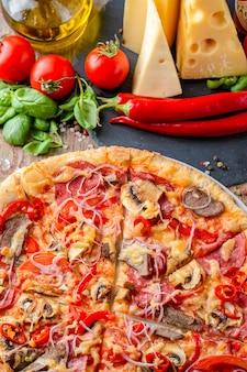 Pizza italienne et ingrédients sur un fond en bois, vue de dessus